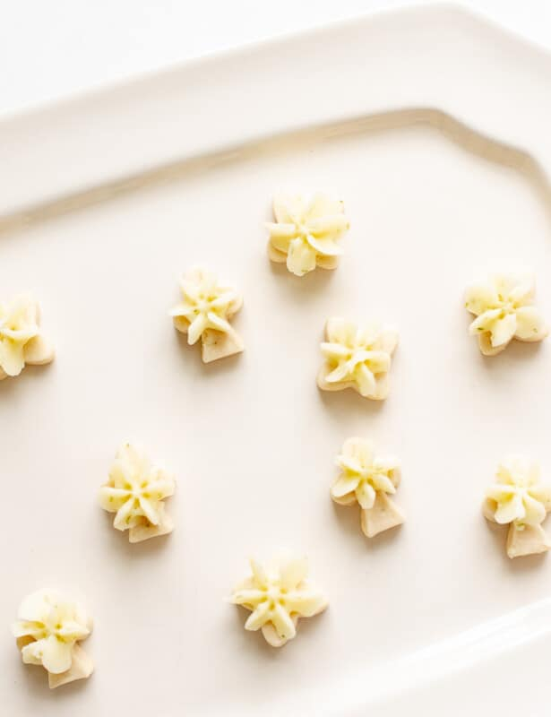 A white plate with cute little lime cookies topped with lime frosting.