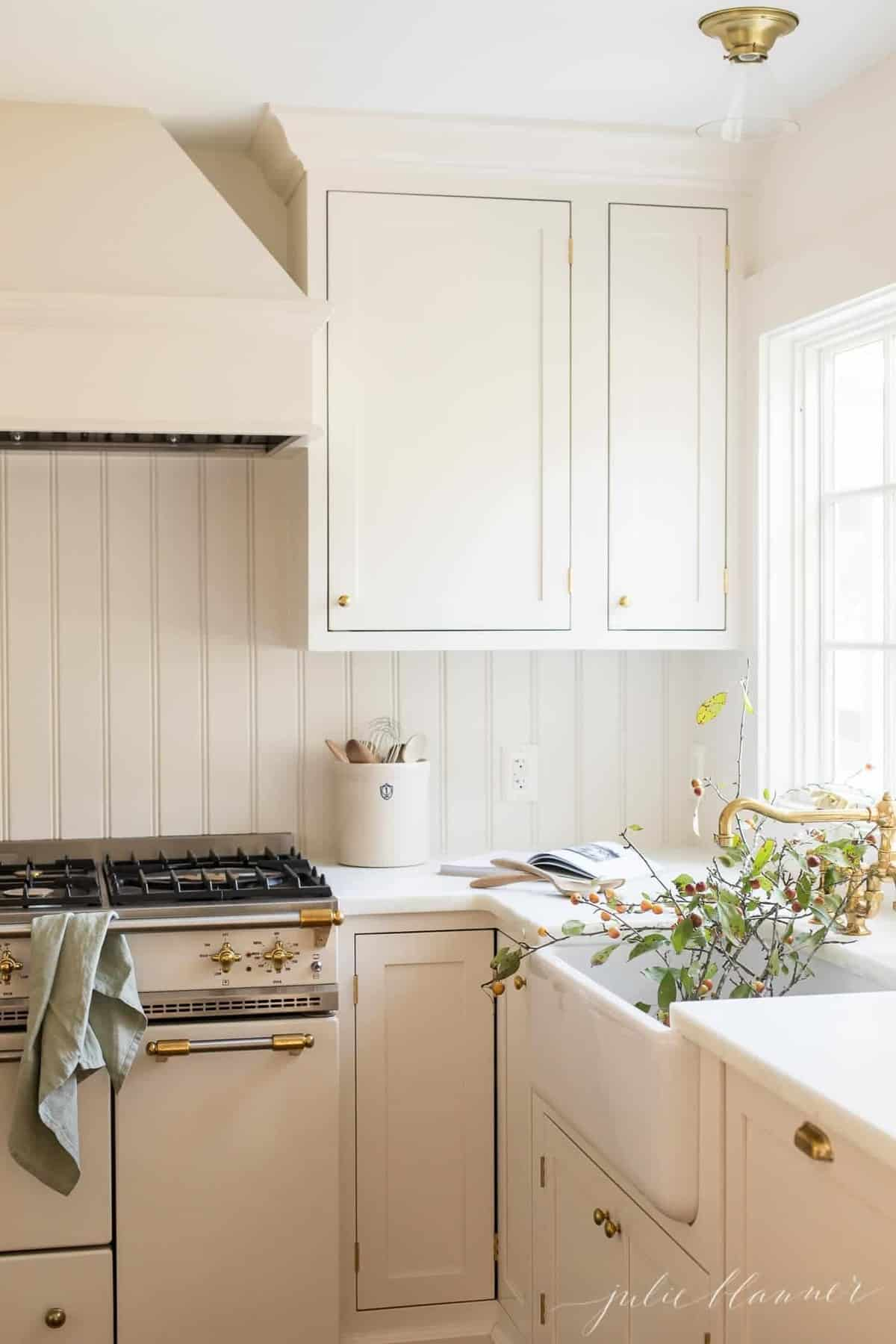 A cream kitchen with a white farmhouse sink, branches inside for fall decorating.