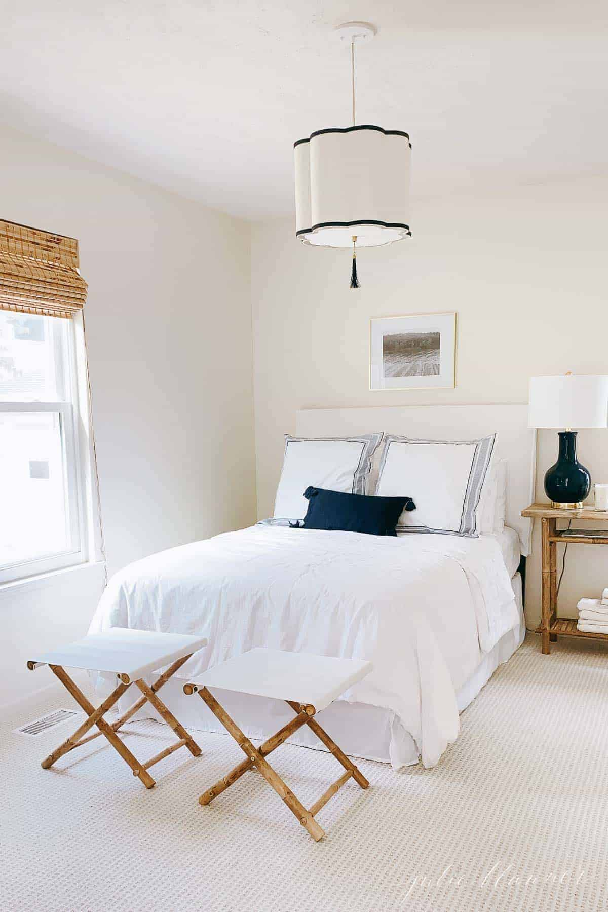 white and navy bedroom with pendant light
