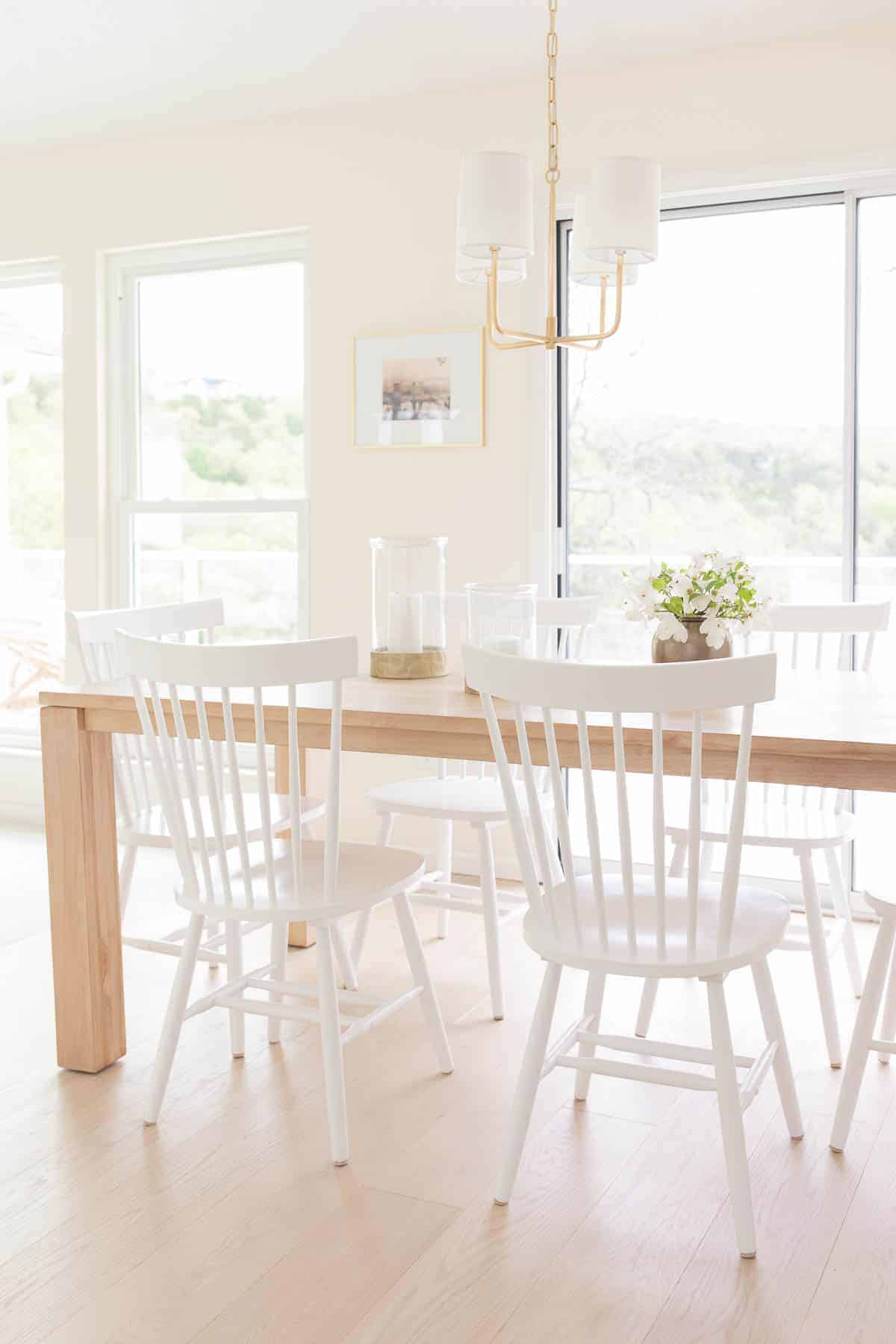 eat in kitchen with teak table white chairs and gold chandelier