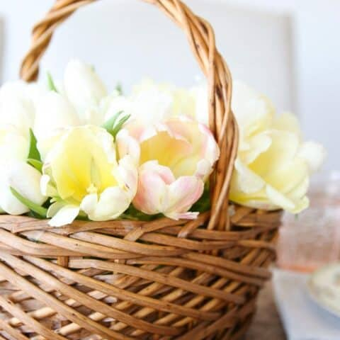 A wicker flower basket filled with yellow tulips.