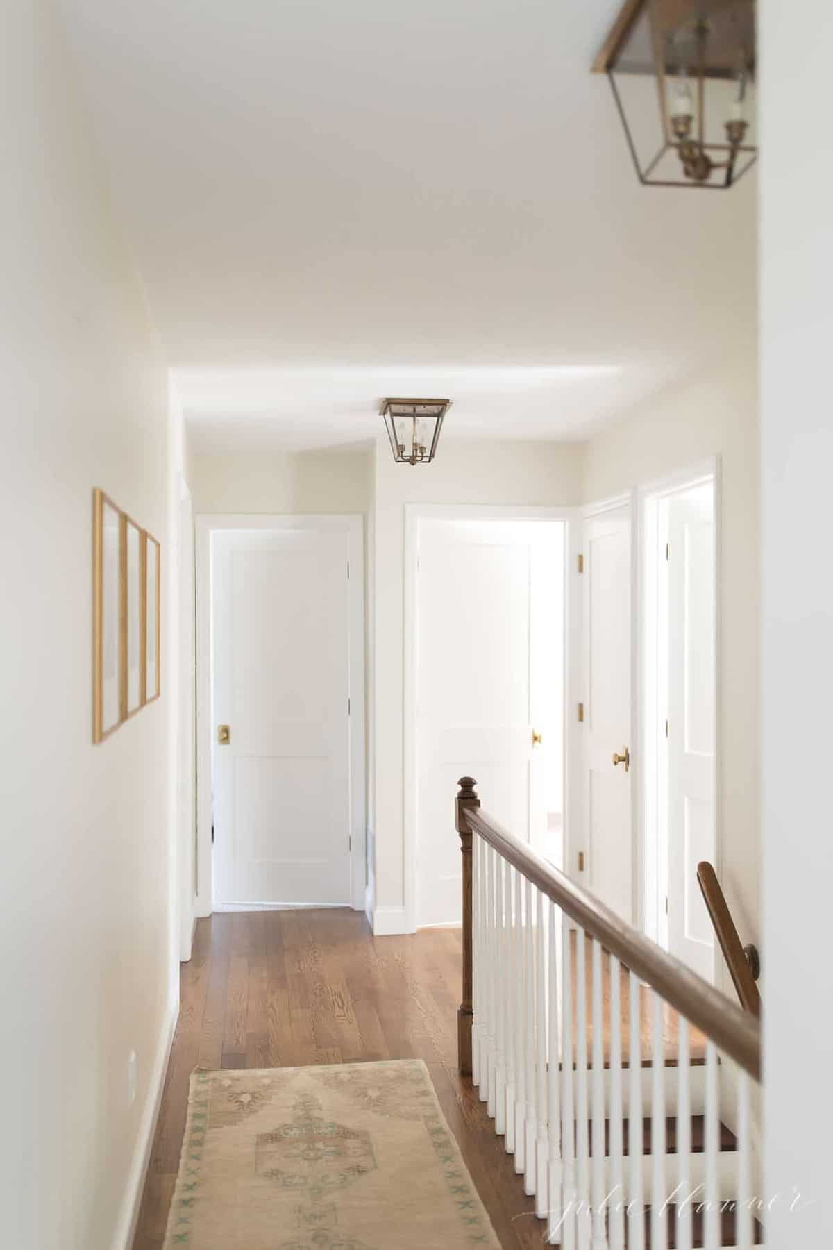 A white upstairs hallway in a home with a Kilim rug on the floor.