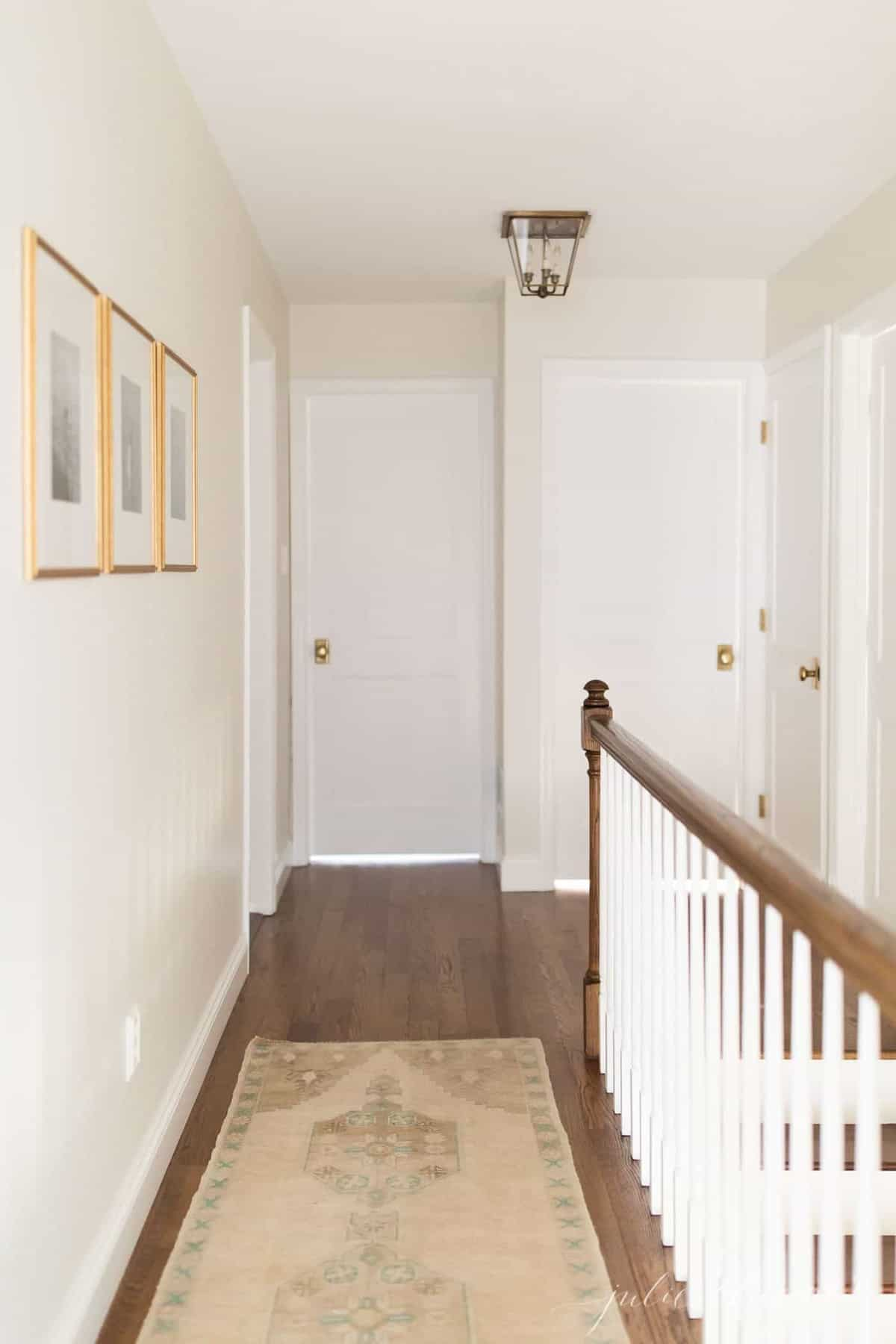 A white upstairs hallway in a home with a turkish rug on the floor.