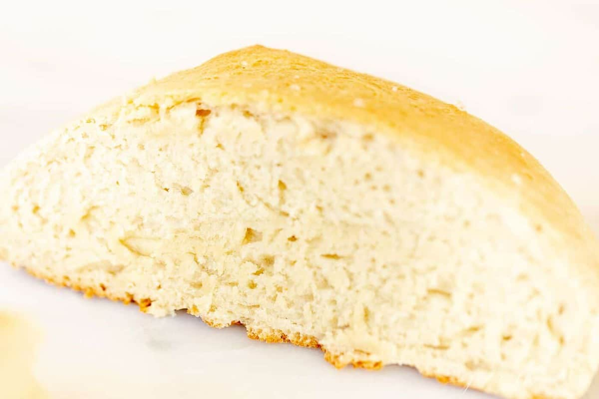 A slice of homemade bread made with rapid rise yeast on a marble surface.
