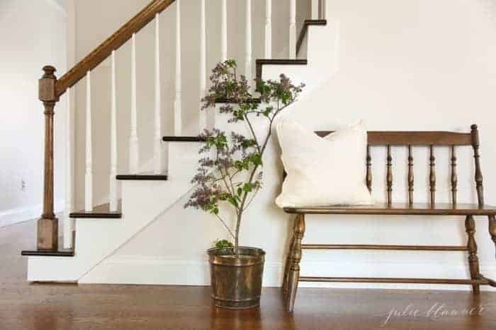 An entryway with white walls, a wooden bench and wooden stairs in a home with character.