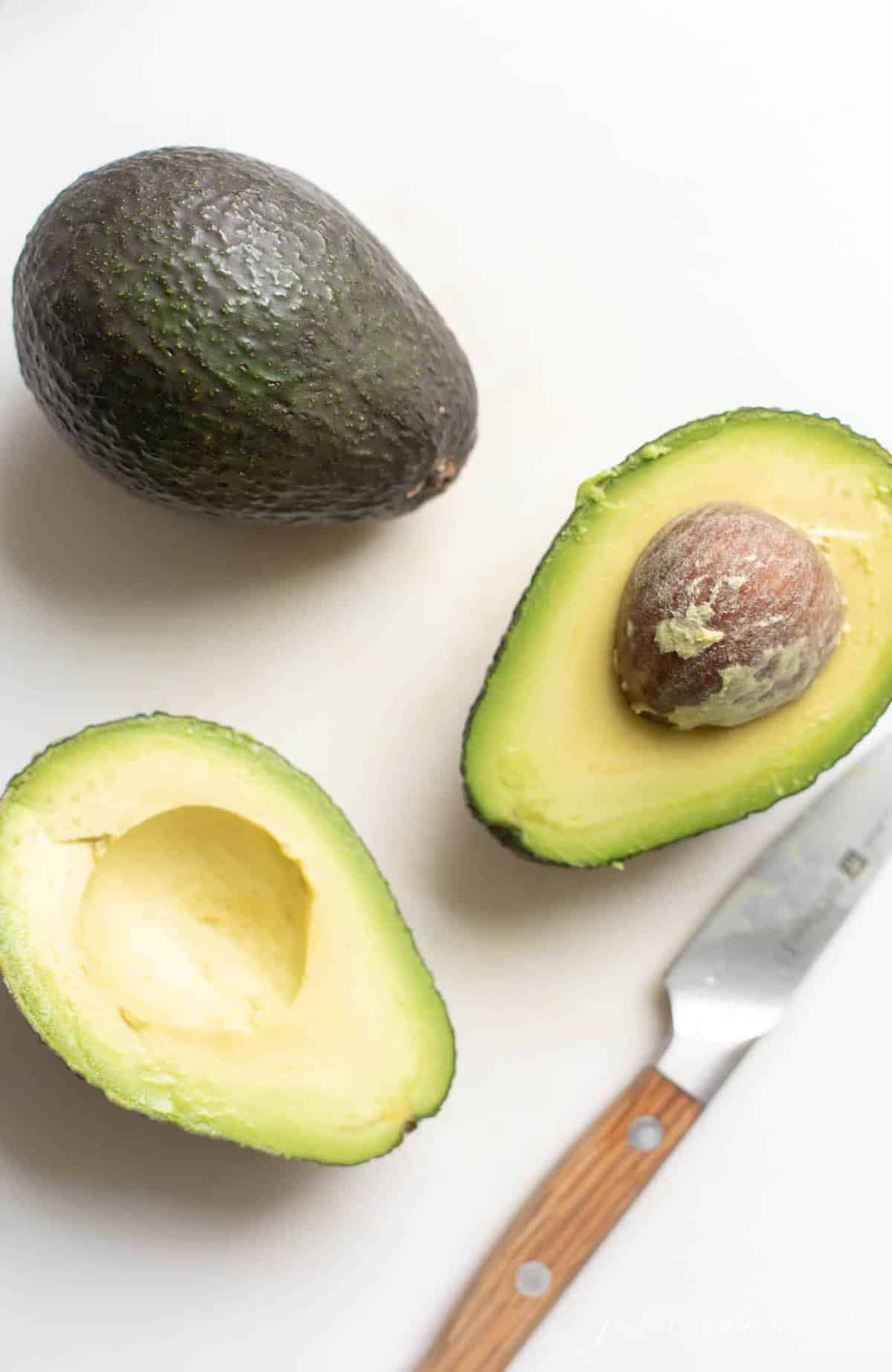 A white surface with two avocados, one sliced open with a knife to the side.