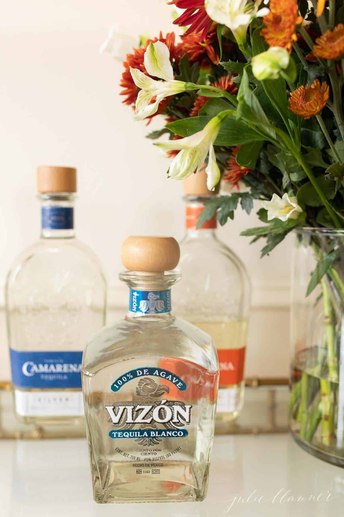Three clear glass bottles of the best tequila for margaritas on a glass bar cart, flowers to the side.