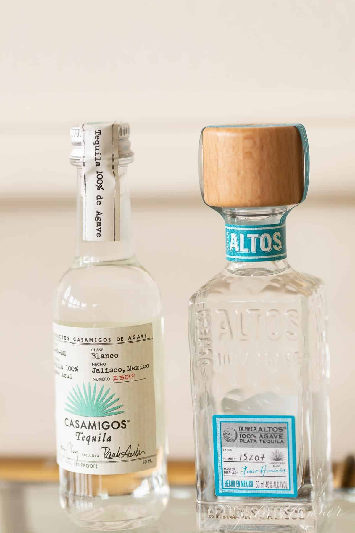 Two clear glass bottles of tequila for margaritas, on a glass bar cart.