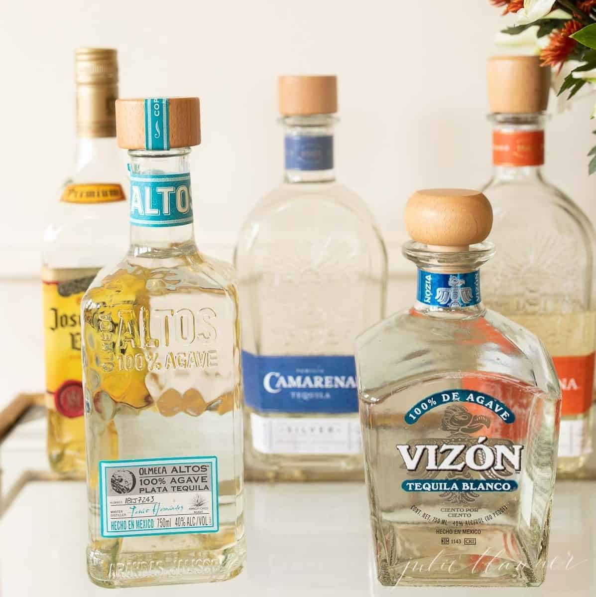 Five bottles of tequila on a clear glass bar cart.
