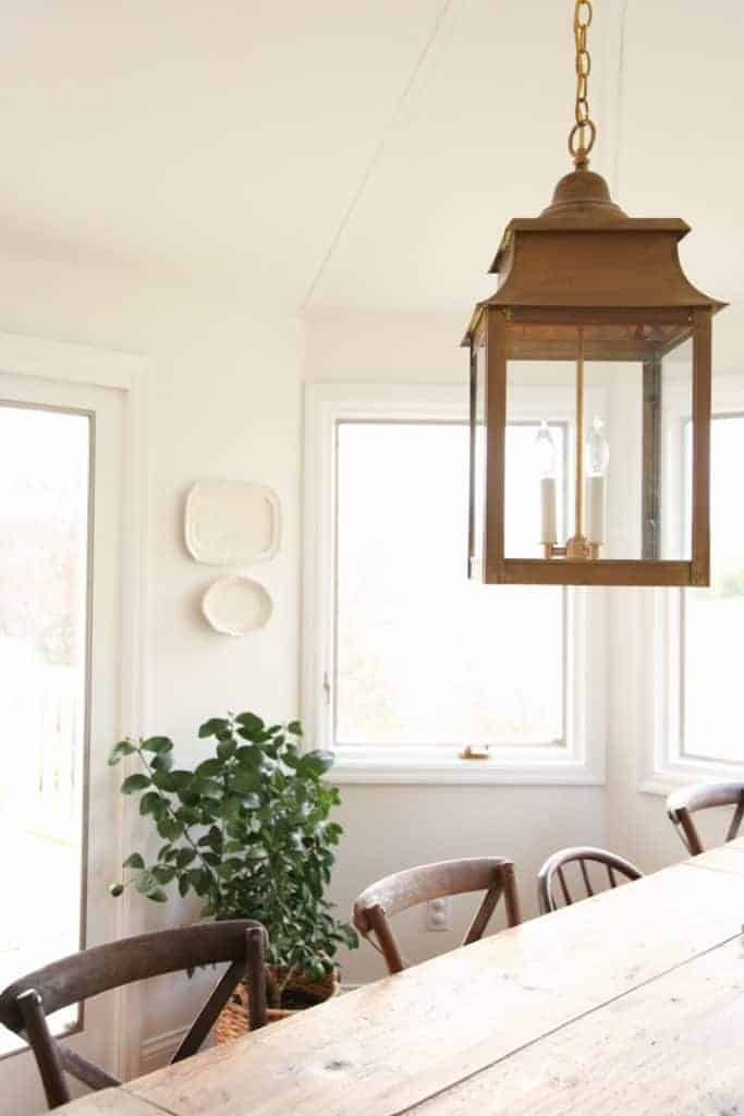 A brass lantern hanging in a white dining room in a character home.