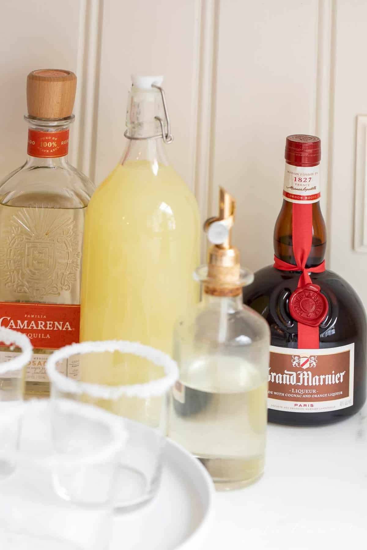 A set up of bottles preparing to make margaritas, with expensive tequila bottle