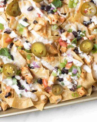 A sheet pan full of delicious chicken nachos for a cinco de mayo menu item