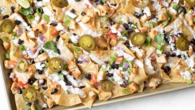 A sheet pan full of delicious chicken nachos for a cinco de mayo menu item