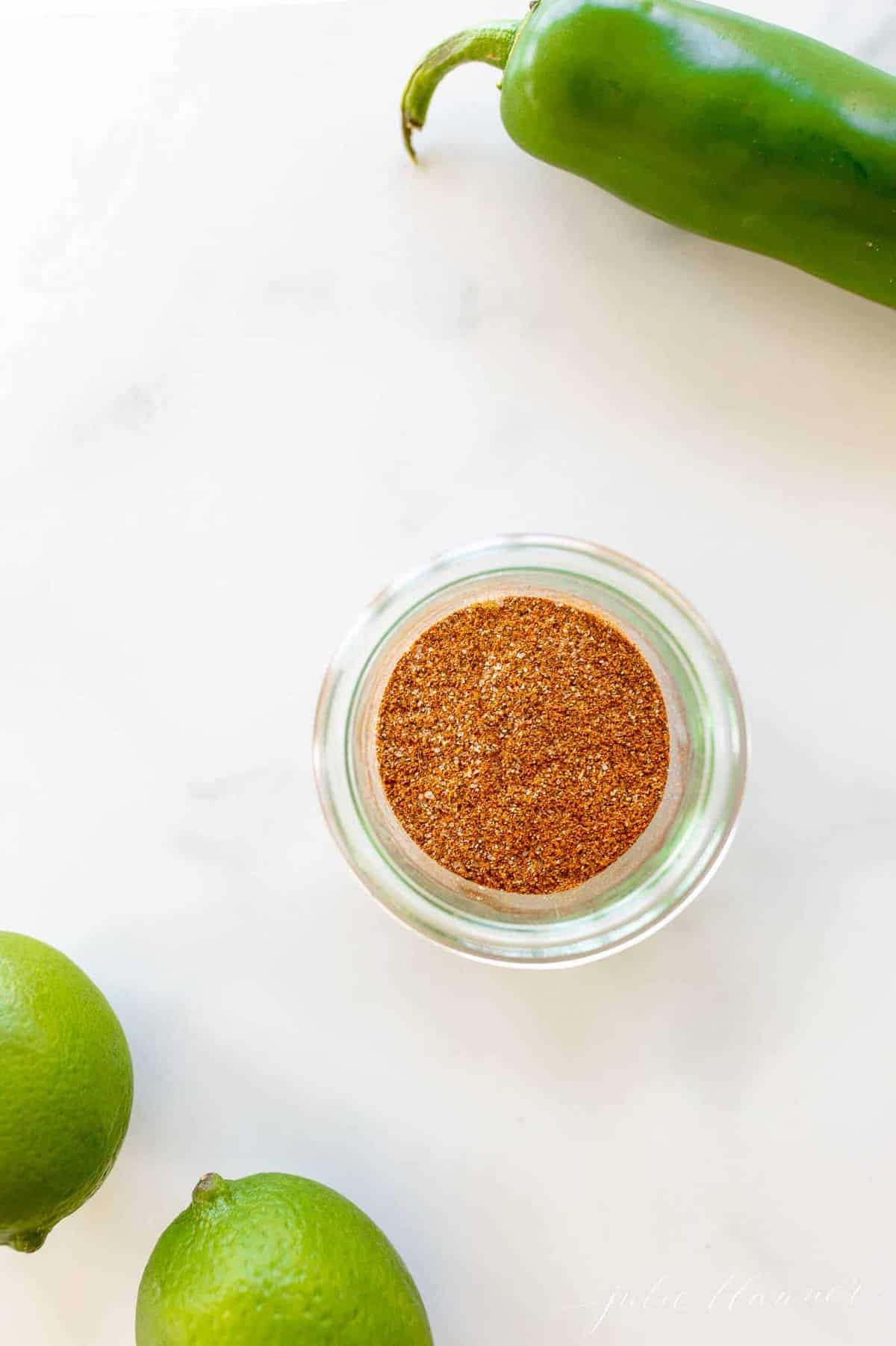 Marble surface with a clear jar full of fajita seasoning, limes and jalapeno to the side.