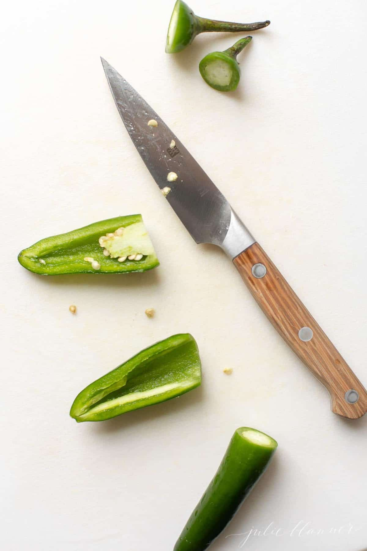 A white surface with a sliced jalapeno, knife to the side.