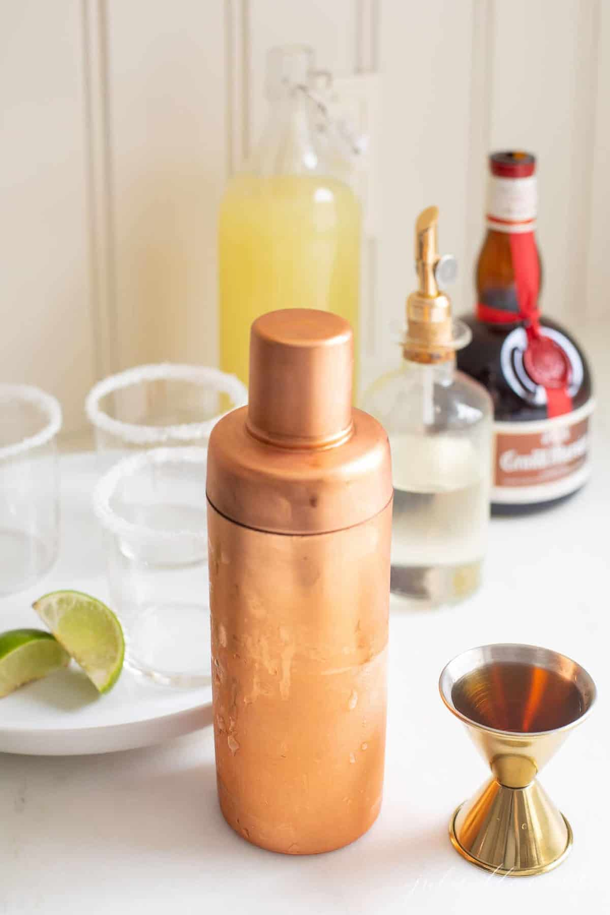 A copper cocktail shaker with all the ingredients for margaritas from scratch surrounding.