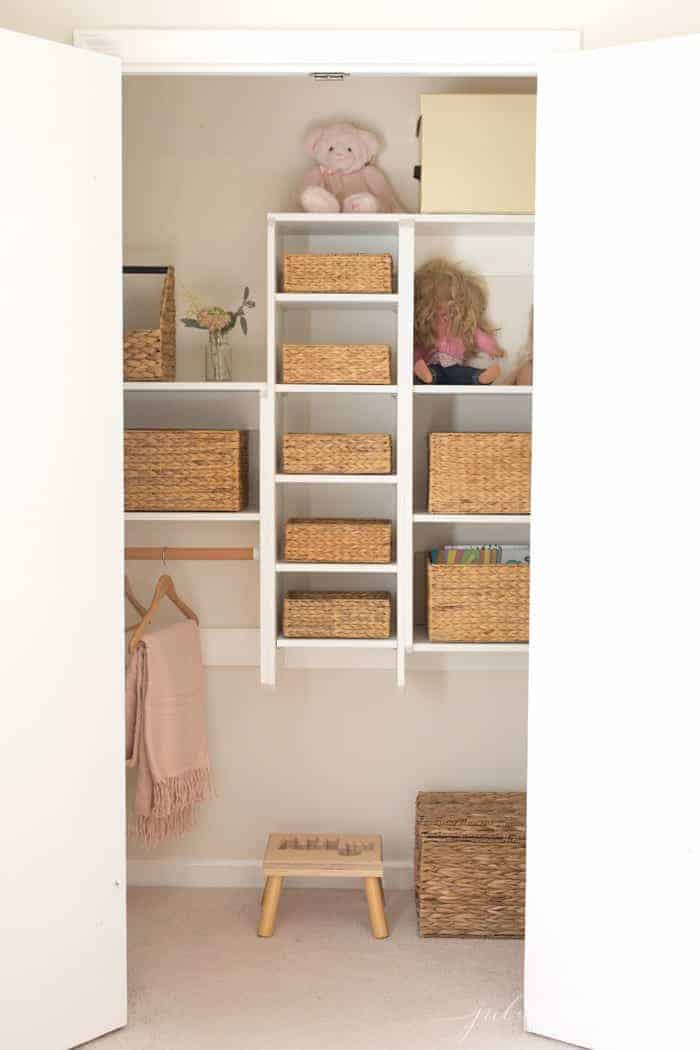 An organized child's closet filled with matching seagrass woven baskets.