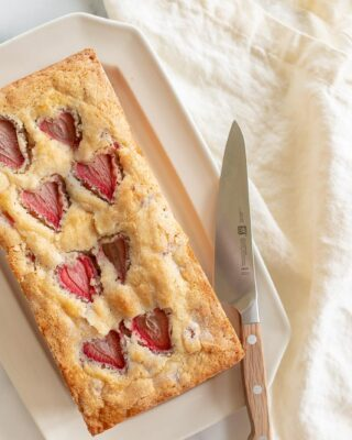 An ivory platter with a fresh loaf of strawberry bread, knife to the side.