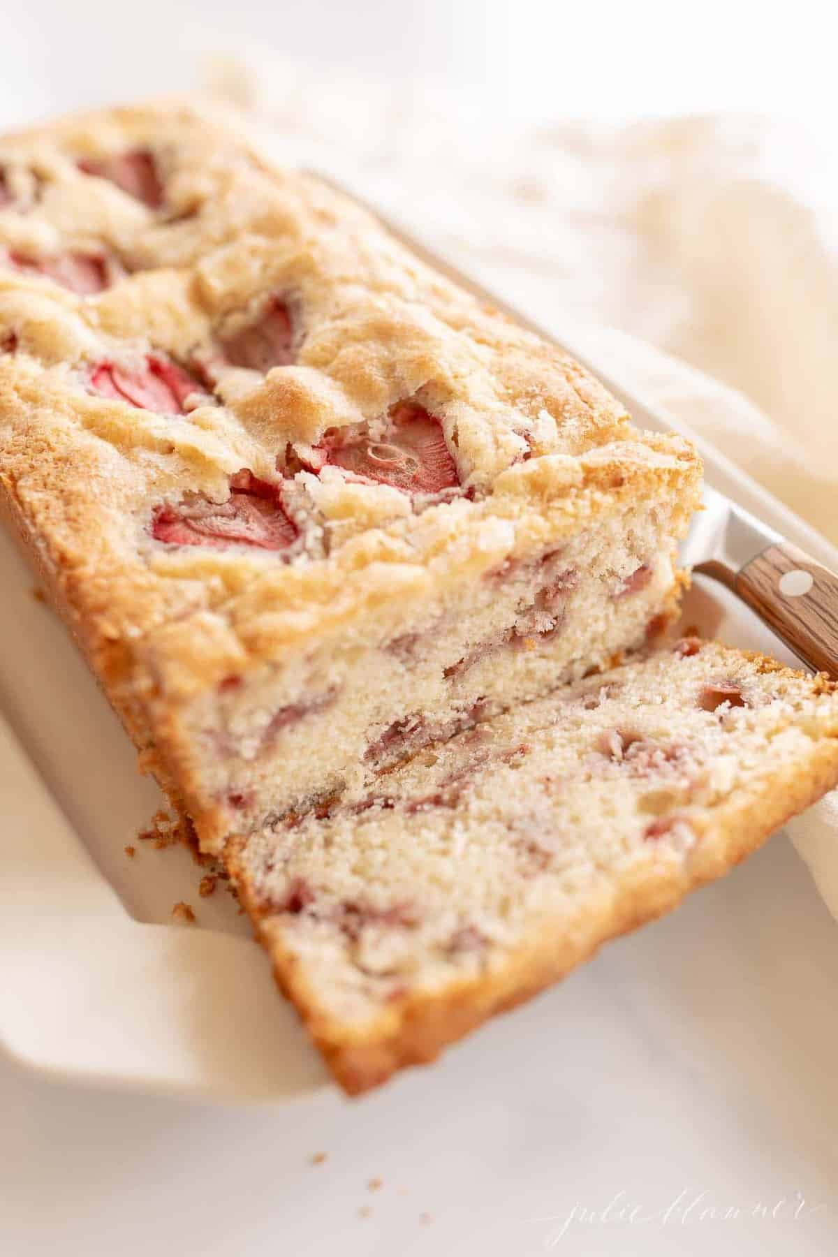 A loaf of strawberry bread, first slice cut off, knife to the side.