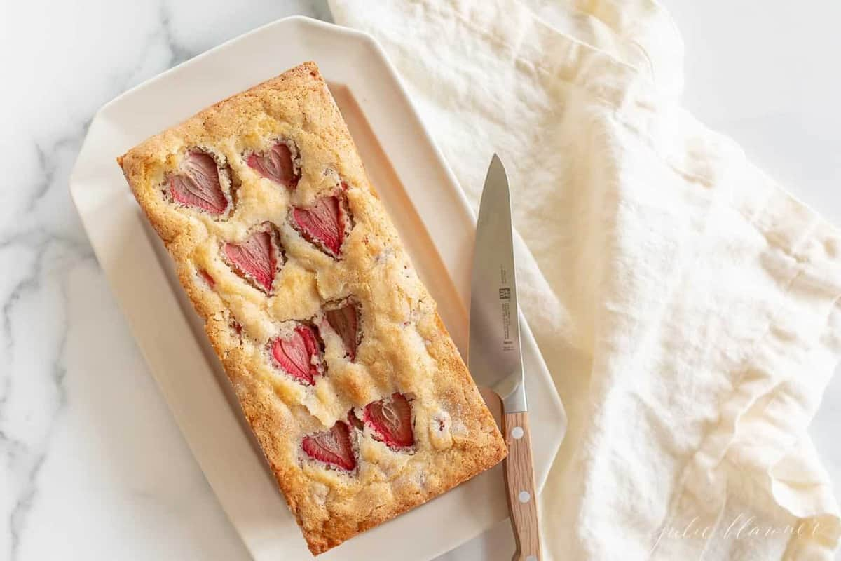 Strawberry bread on a white platter, a knife and linen napkin to the side.