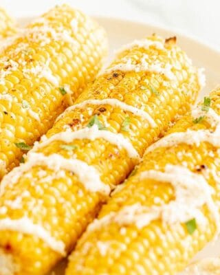A white platter with an elote recipe of three mexican corn on the cobs, drizzled with cream sauce and cilantro.