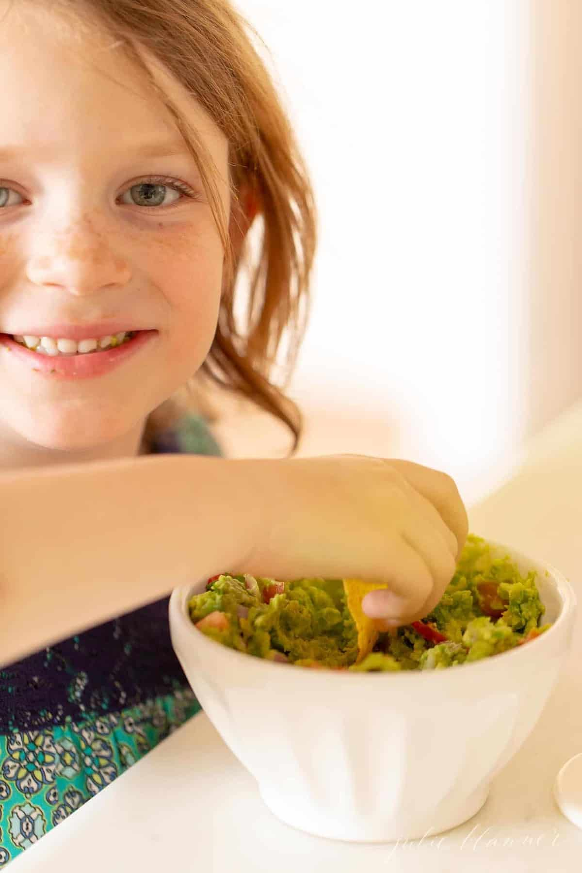 A little girl dipping into a bowl of homemade fresh guacamole.