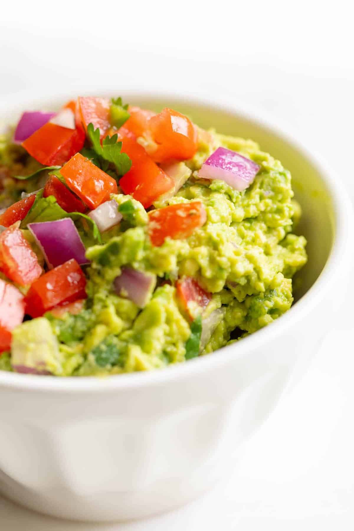 A white bowl on a white surface, filled with a homemade guacamole recipe.