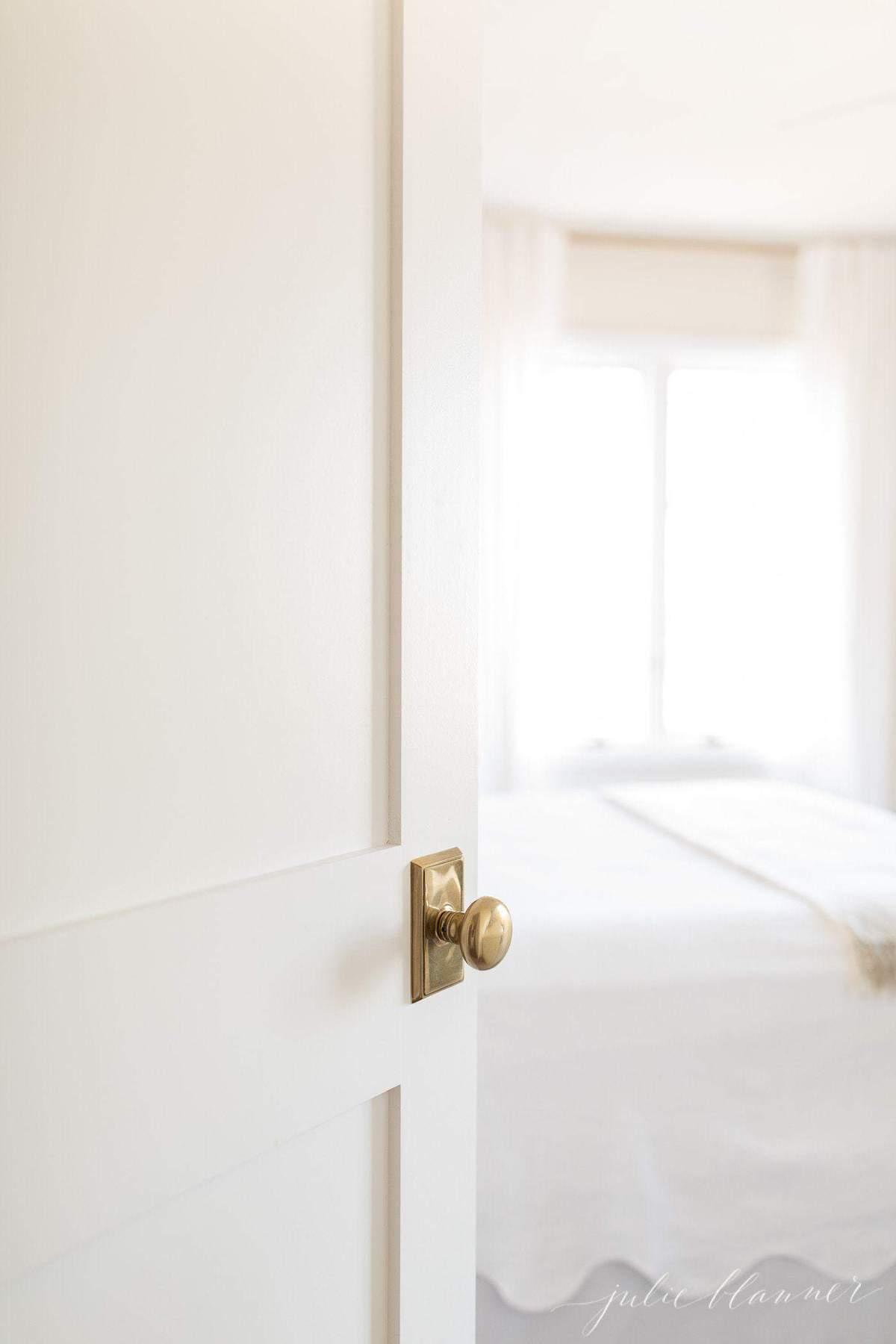 A new door with a brass doorknob peeking into a guest bedroom.