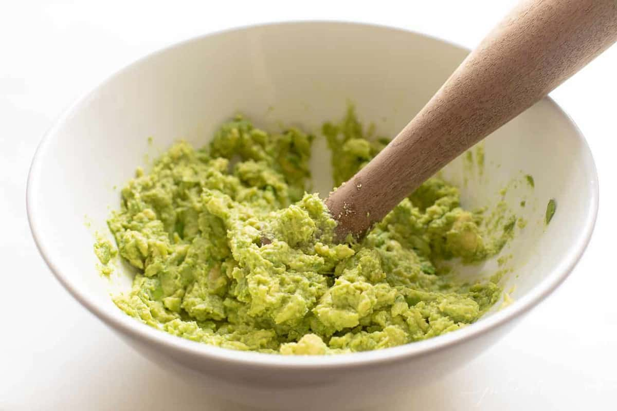 A white bowl with mashed avocados and a wooden spoon, starting a homemade guacamole recipe.