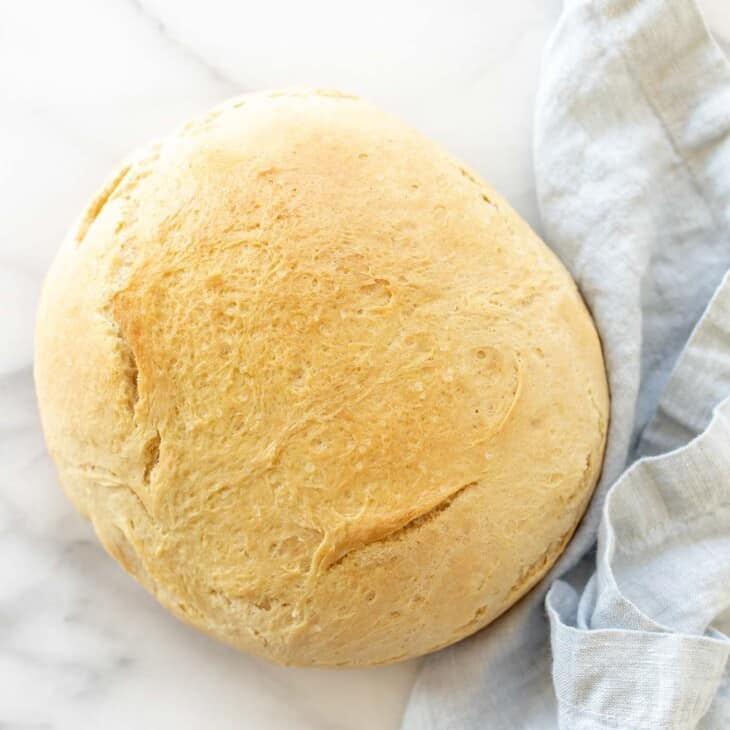 A marble surface with a round loaf of homemade bread, blue linen napkin to the side.