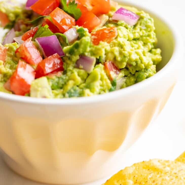 A white bowl full of homemade guacamole, chips to the side.