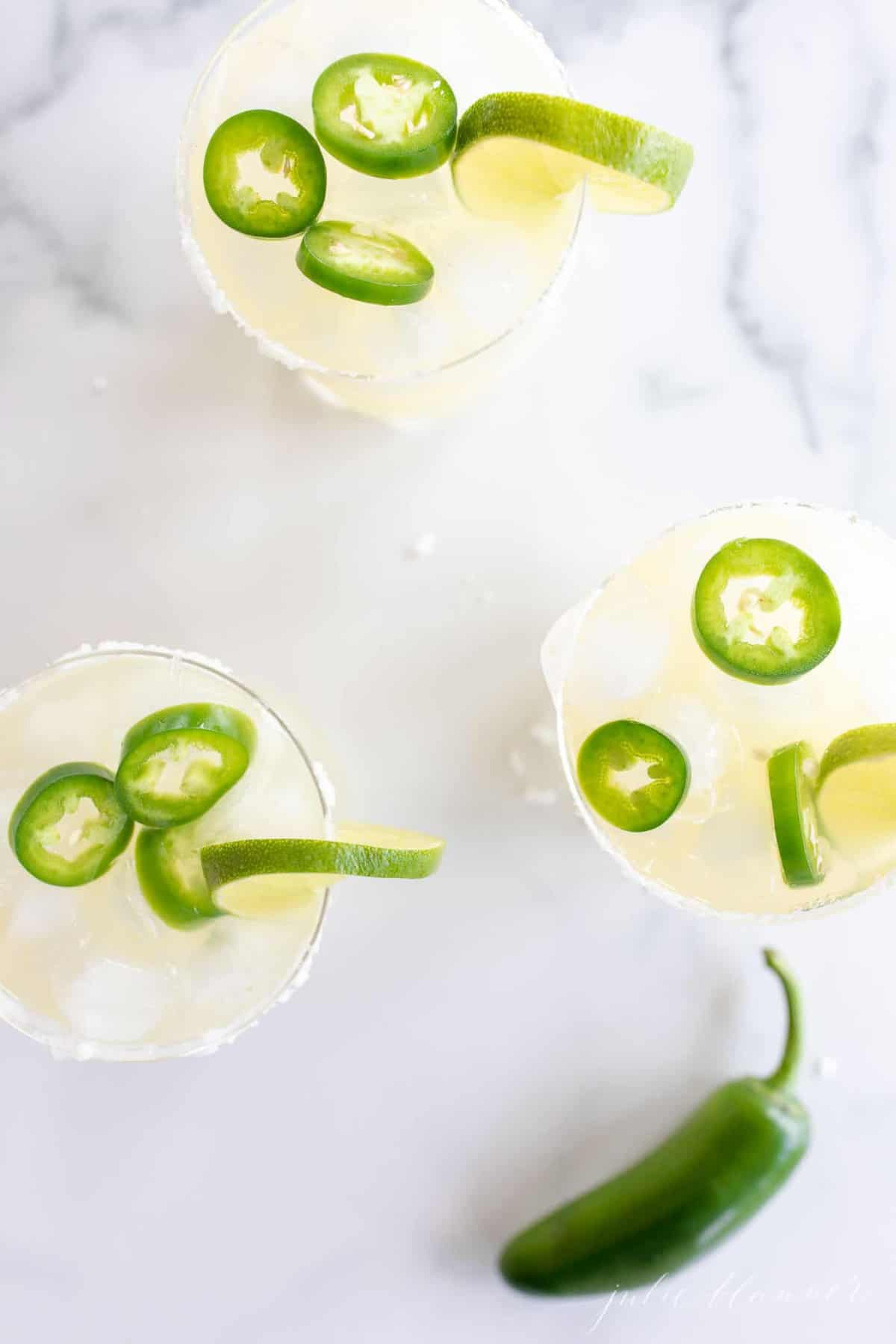 Marble surface, three glasses full of jalapeno margaritas.