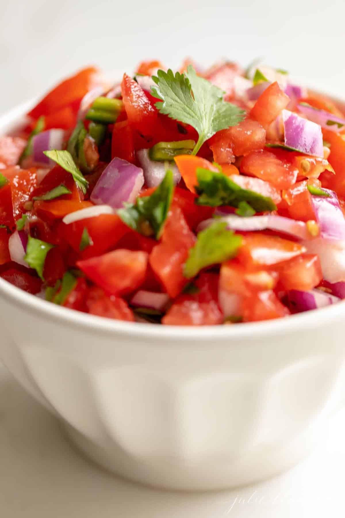 A white bowl filled with fresh pico de gallo.