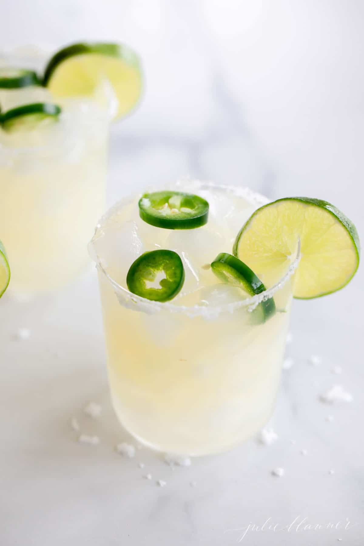 A marble surface with clear glasses full of spicy margarita recipe