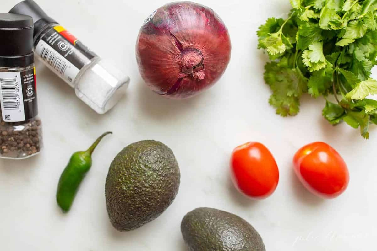 A white surface filled with the fresh ingredients for a guacamole recipe.