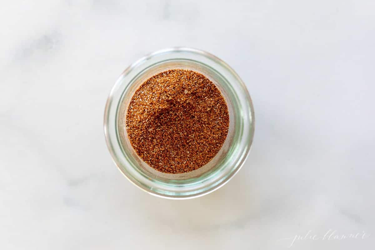 A marble surface with a clear glass jar full of homemade fajita seasoning mix.