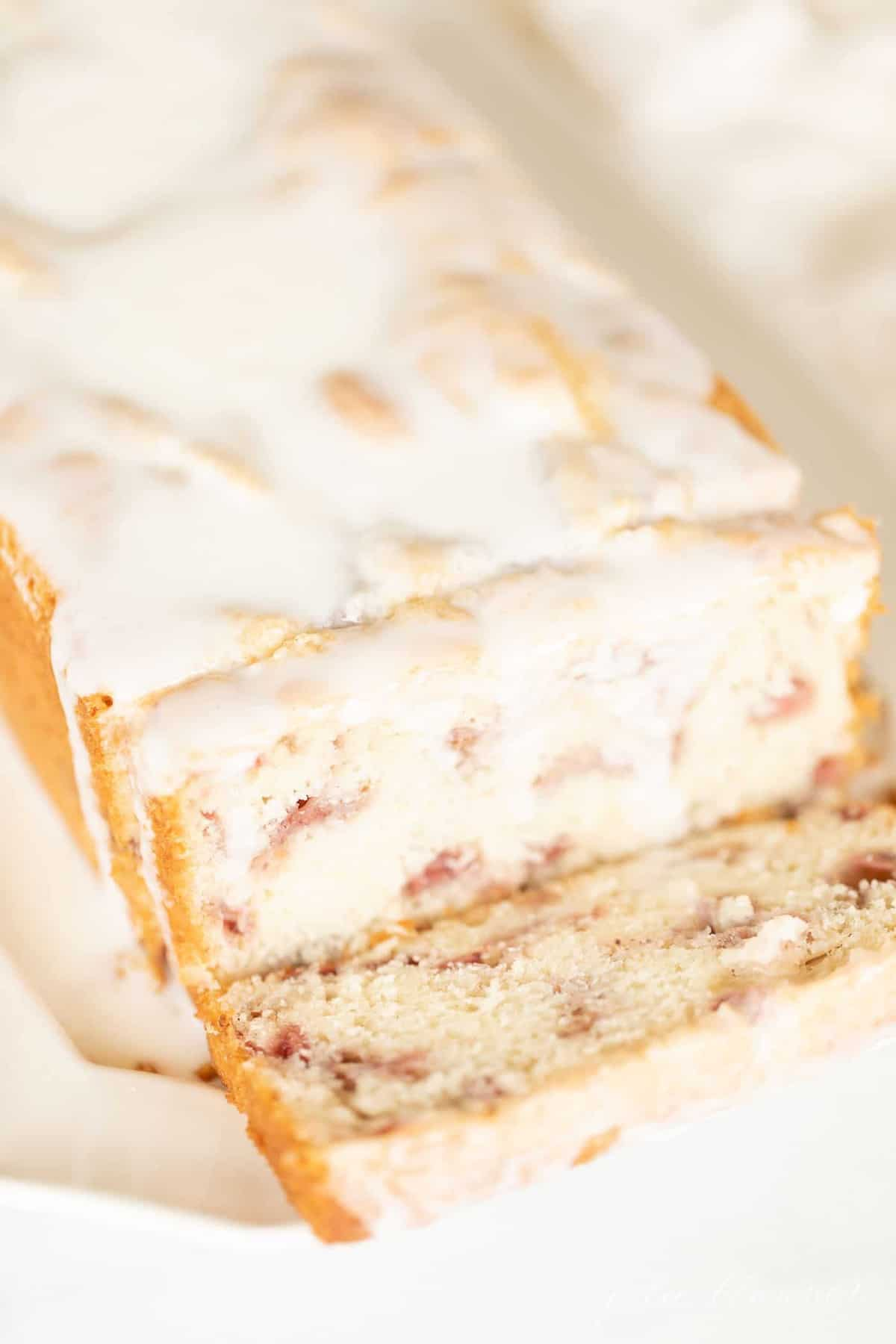 A sliced loaf of glazed strawberry quick bread on an ivory platter.