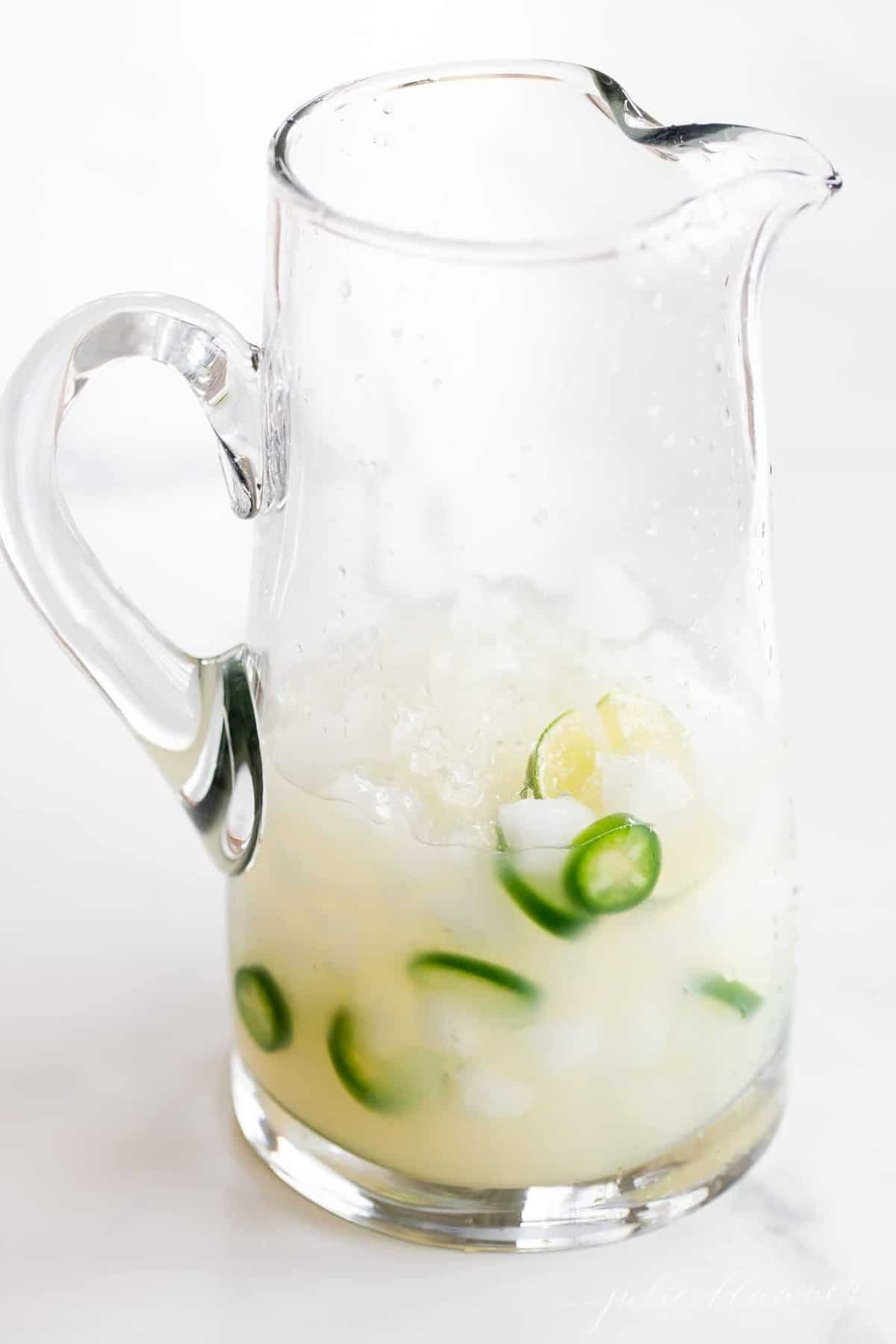 A clear glass pitcher full of spicy jalapeno margaritas, sliced jalapenos and limes floating in the ice.