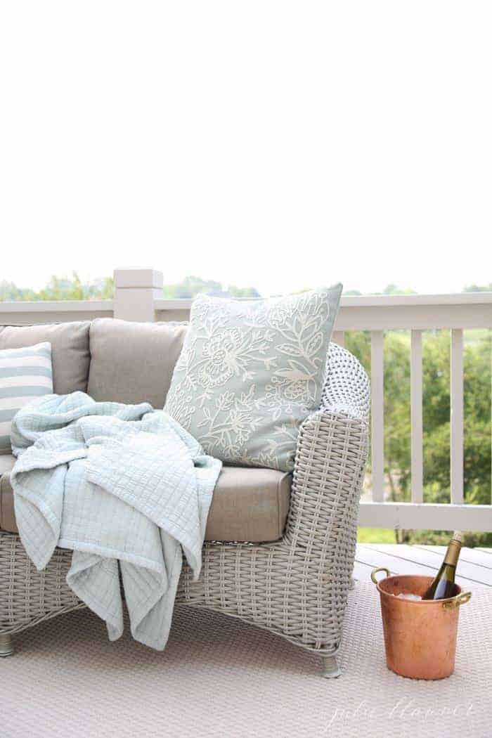 A wicker sofa on a white painted deck in an outdoor living room.