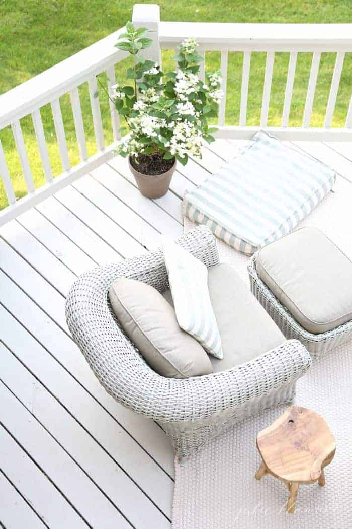 A white painted deck in an outdoor design with wicker furniture.