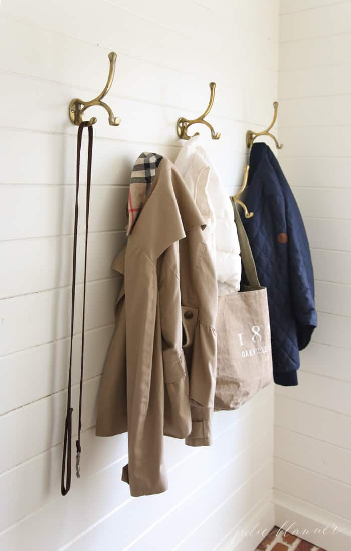 A white horizontal paneled mudroom with brick floors, brass hooks holding jackets and dog collar.