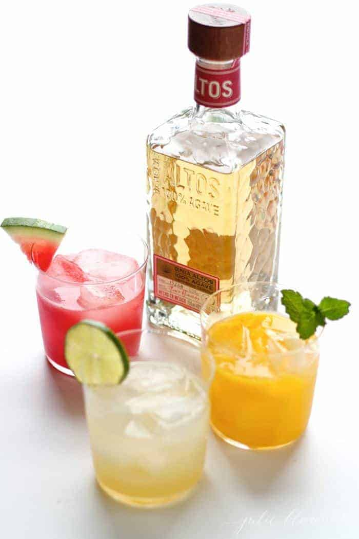 A white surface with a bottle of gold tequila and margarita glasses