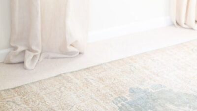 A white bedroom with a vintage turkish rug on carpet.