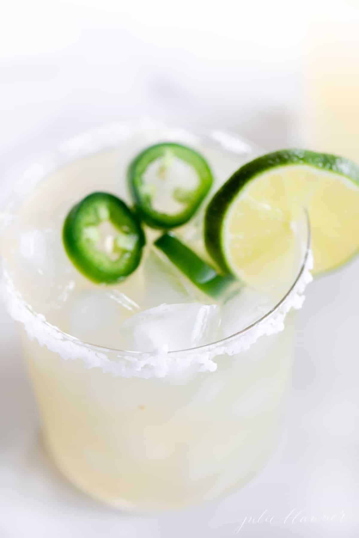 looking down into a clear glass full of spicy margarita topped with sliced jalapeno and lime.