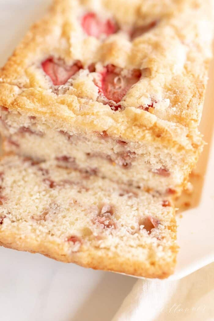 A close up of a loaf of strawberry bread loaf, sliced.