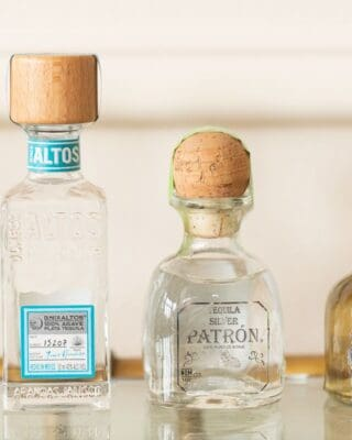 Four bottles of the best tequila for margaritas on a glass bar cart.
