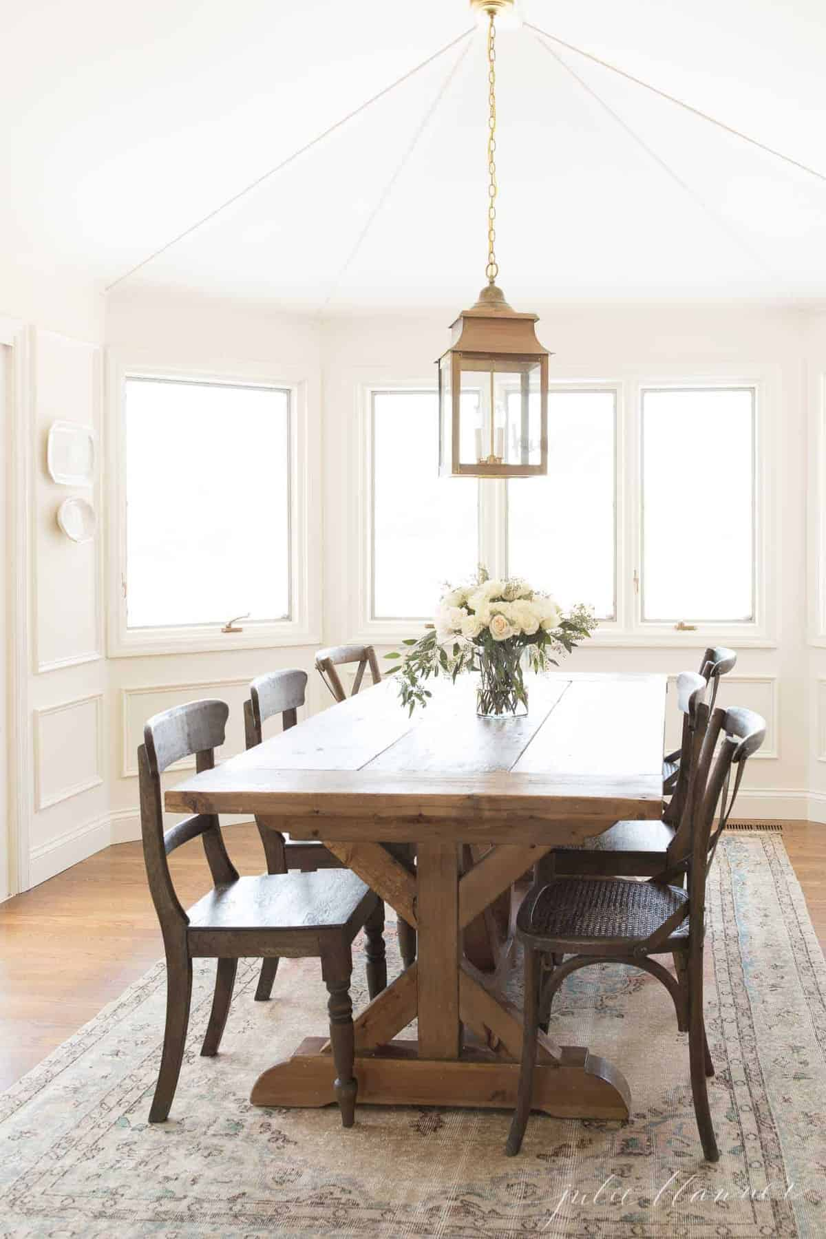 A white dining room with a farm table and a vintage kilim style Turkish rug.