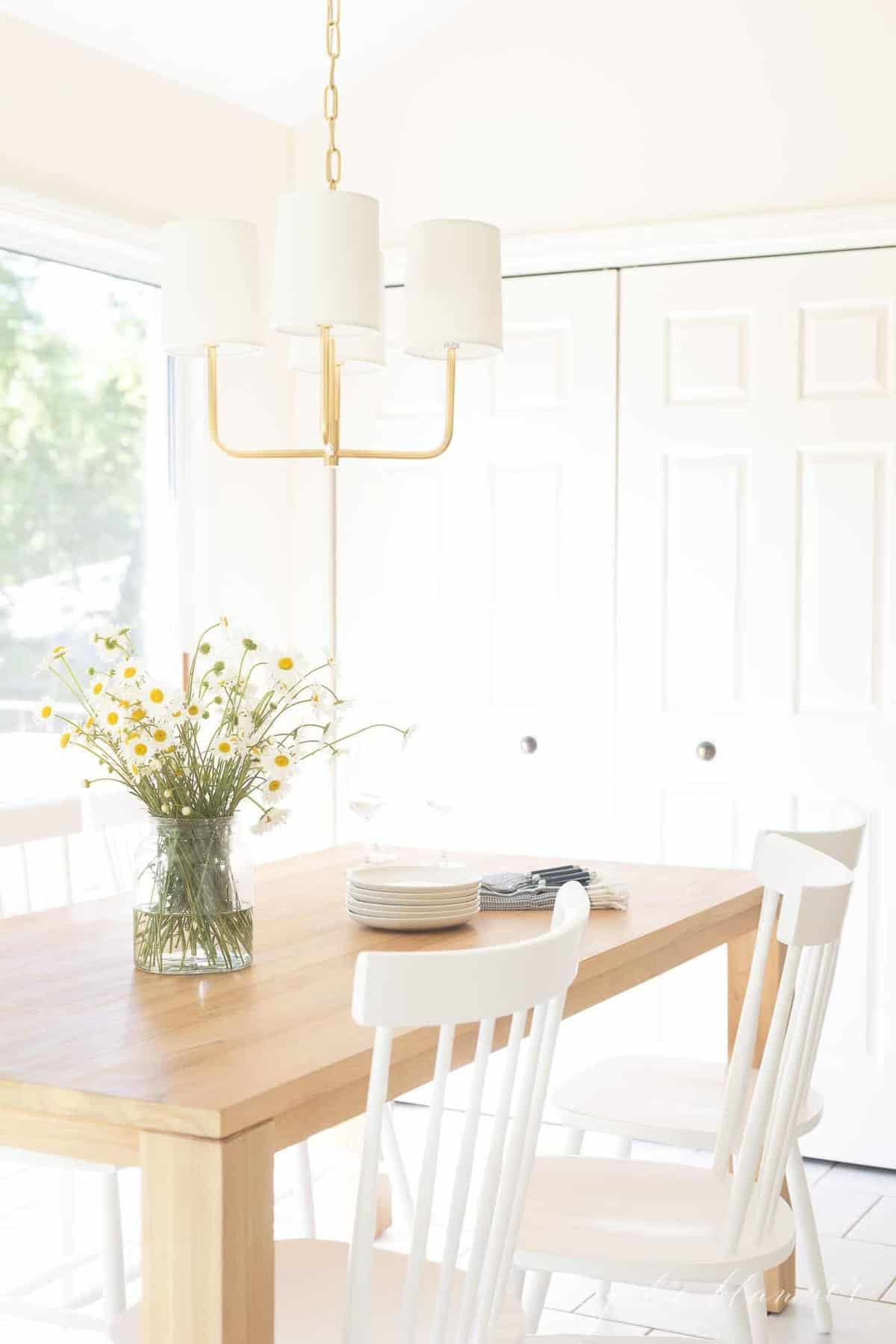A bright white kitchen with a wood table and a brass chandelier.