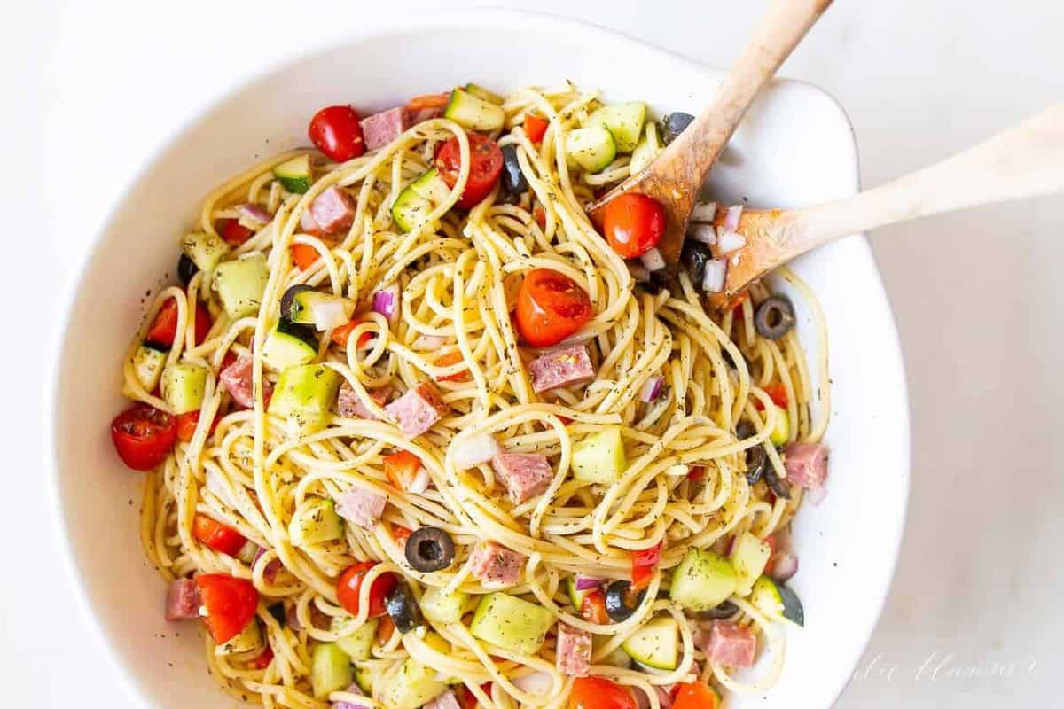 A white bowl with spaghetti salad, wooden spoons to the side.