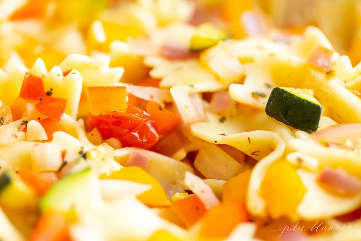 A white bowl filled with a fresh vegetarian pasta salad.